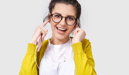 Closeup shot of happy young woman using mobile phone to listening the music. Positive female enjoying the songs on earphones using her smart phone. People and technology concept Stock Photo