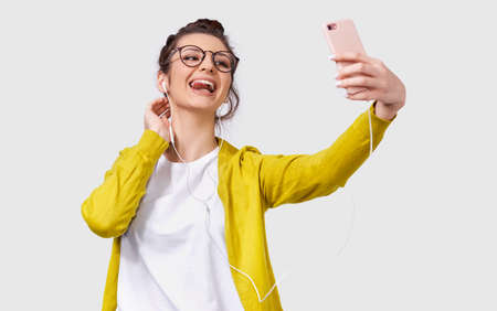 Young European woman in casual clothes standing and taking a selfie isolated over white studio background. Pretty Caucasian female wearing transparent spectacles making self portrait