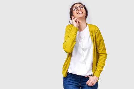 Studio horizontal shot of pretty Caucasian young woman smiling broadly, listening the music on headphones. Happy female enjoying the favorite songs on earphones. People, music and technology concept Stock Photo