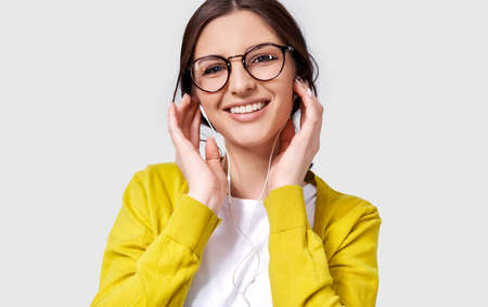 Closeup shot of pretty Caucasian young woman smiling broadly, listening the music on headphones. Happy female enjoying the favorite songs on earphones. People, music and technology concept