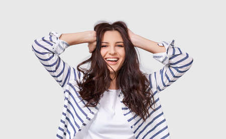 Indoor image of beautiful brunette young woman with long hair smiling cheerfully. Charming female smile broadly showing her white healthy teeth to camera while feeling happy and carefree. People 版權商用圖片