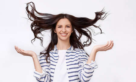 Studio image of beautiful young woman with flying hair smiling broadly and looking at he camera with raised hands, posing over white background. Charming brunette female with beautiful long hair 版權商用圖片