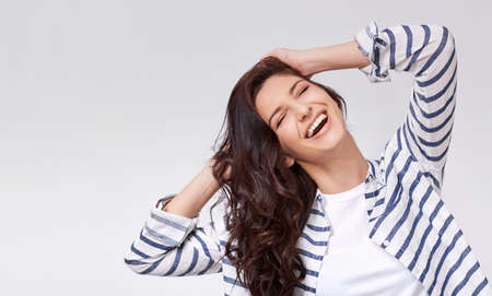 Studio shot of beautiful brunette young woman with long hair smiling broadly in striped shirt. Charming female smile broadly showing her white healthy teeth to camera while feeling happy and carefree