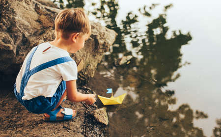 Horizontal rear view of cute little boy launch paper ship on the lake in the park. Adorable kid boy playing with a boat. Child sailing a toy boat by the waters edge outdoors. Childhood and ecology Banque d'images - 132967115