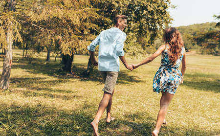 Rear view of romantic couple in love dating outdoors at the park on a sunny day. Happy couple in love walking and playing together on the grass in the nature background. Valentines day. Couple goals