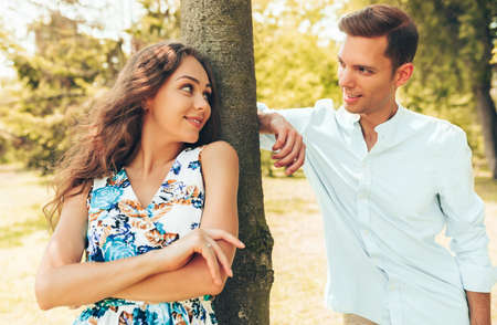 Young couple looking to each other with love. Portrait of man and woman posing outdoors in the park. Stock Photo