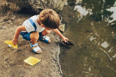 Lovely little boy launches paper ship on the lake in the park. Adorable kid boy playing with a boat. Child sailing a toy boat by the waters edge outdoors. Childhood and ecology Banque d'images - 132967385