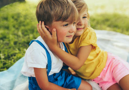 Candid image of smiling two children playing and enjoying the sumemrtime on the blanket outdoors. Sister hugging her little brother in the park. Kids having fun on sunlight.
