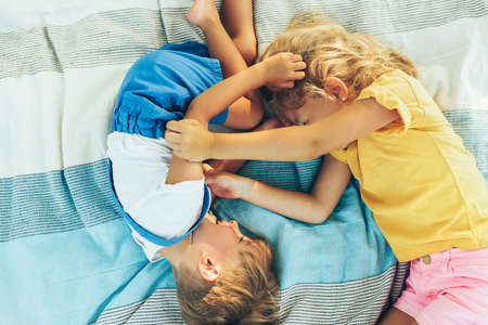Happy children lying on the blanket outside. Happy little boy and little girl enjoying summertime in the park. Adorable kids playing and having fun on sunlight outdoors. Sister and brother. Childhood Stock Photo