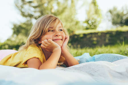 Image of adorable blond little girl playing at nature background. Happy child enjoying summertime in the park. Cheerful kid relaxing in the forest on sunlight outdoors. Happy childhood.