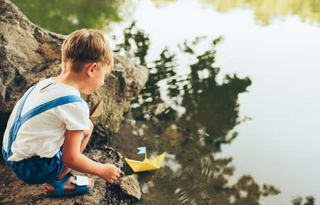 Rear view image of cute little boy launch paper ship on the lake in the park. Adorable kid boy playing with a boat. Curious child sailing a toy boat by the waters edge outdoors. Childhood and ecology