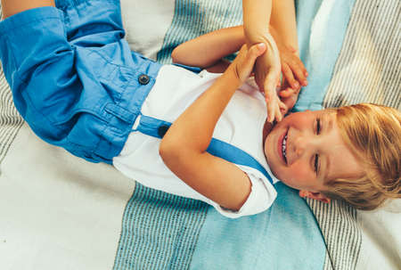 Little boy laughing and lying on the blanket. Handsome kid smiling broadly and having fun on sunlight outdoors. Happy child enjoying summertime in the park. Happy childhood. Stock Photo