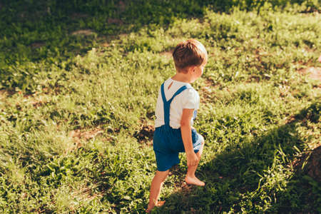 Horizontal outdoors rear view image of happy little boy wearing blue shorts playing at sunlight and nature background. Cheerful child running on the green grass in the park. Kid having fun. Childhood