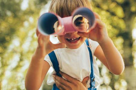 Immagine del primo piano del ragazzino carino che gioca con un binocolo alla ricerca di un'immaginazione o di un'esplorazione in una giornata estiva nel parco. Bambino felice che gioca a fingere il gioco di safari all'aperto nella foresta. Infanzia