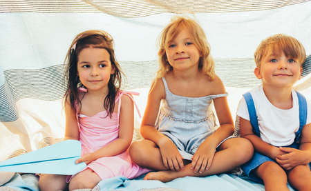 Cute children sitting on the blanket, playing together. Happy little boy and little girls smiling and relaxing in the park. Cheerful kids playing outdoors