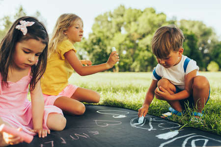 Outdoors image of kids sitting on the green grass playing with colorful chalks. Happy children drawing with chalks in the park. Friends, boy and two girls having fun on sunlight outdoor. Childhood