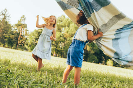 Outdoors image of children playing under the blanket, jumping and dancing together. Happy little boy and little girl enjoying summer day in the park. Cheerful kids playing outdoors. Childhood concept 写真素材