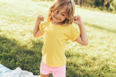 Adorable blond little girl playing at nature background. Happy child enjoying summertime in the park. Cheerful kid having fun in the forest on sunlight outdoors. Happy childhood. 版權商用圖片