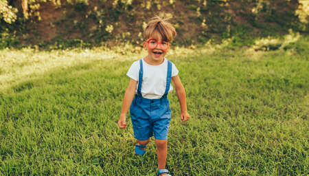 Happy little boy wearing blue shorts and red glasses playing at nature background. Cheerful child running on the green grass in the park. Kid having fun on sunlight outdoors. Happy childhood.