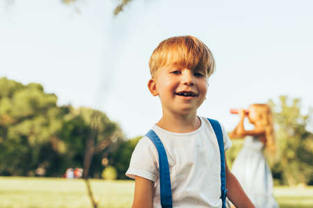 Joyful little boy playing in summer day in park. Happy child playing outdoors games on green grass. Childhood concept