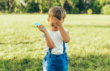 Little boy wearing blue shorts, covering his eyes with hand, playing hide and seek at nature background. Cheerful child playing in the park. Kid having fun on sunlight outdoors. Happy childhood.