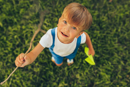 Top view image of cute kid playing with a paper plane in summer day in park. Happy little boy smiling and playing outdoors games on green grass. Childhood concept