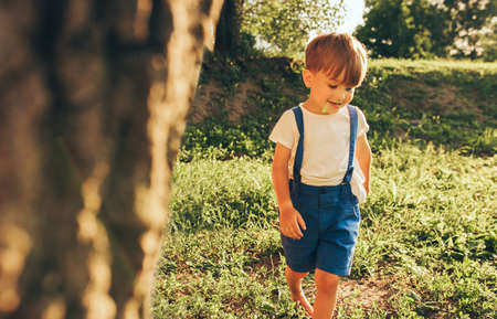 Image of happy little boy wearing blue shorts smiling and playing at sunlight and nature background. Adorable child running on the green grass in the park. Kid having fun. Childhood