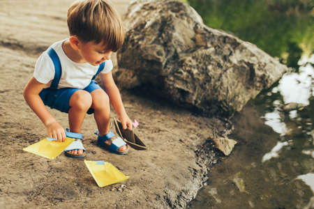 Outdoors image of cute little boy launches paper ship on the lake in the park. Adorable kid boy playing with a boat. Child sailing a toy boat by the waters edge outdoors. Childhood and ecology
