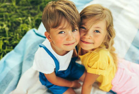 Outdoors close up portrait of smiling two children playing on the blanket outdoors. Little boy and cute little girl bonding and relaxing in the park. Kids having fun on sunlight. Sister and brother