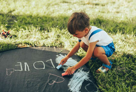 Cute little boy sitting on the green grass playing with colorful chalks. Happy kid drawing with chalks in the park. Childhood concept 写真素材
