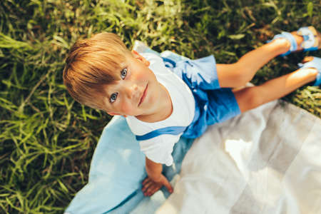 Above view image of cute boy sitting on the blanket and looking to the camera. Happy child enjoying summertime in the park. Handsome kid smiling and relaxing on sunlight outdoors. Childhood Stock Photo