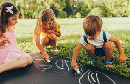 Children sitting on the green grass playing with colorful chalks. Happy little kids drawing with chalks in the park. Friends, boy and two girls having fun on sunlight outdoor. Childhood and friendship