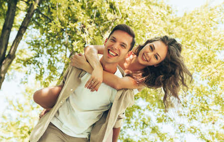 Portrait of young man carrying his beautiful woman on his back at the park, looking at camera. Boyfriend giving piggyback ride to his beautiful girlfriend in a summer holiday. Stock Photo