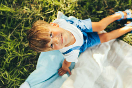 Top view image of cute boy sitting on the blanket and looking to the camera. Happy child enjoying summertime in the park. Handsome kid smiling broadly and having fun on sunlight outdoors. Childhood