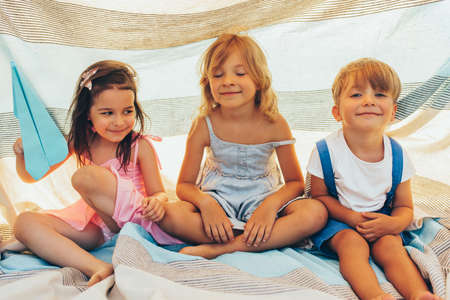 Happy children sitting on the blanket, playing together. Cute little boy and little girls smiling and having fun in the park. Cheerful kids playing outdoors