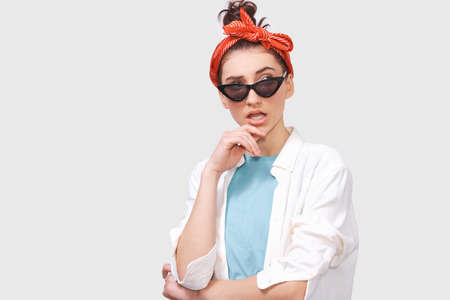 Stylish serious brunette young woman wears black sunglasses, white shirt and trendy red headband, looks seriously directly into camera, poses against white studio background. People emotions concept Stock Photo