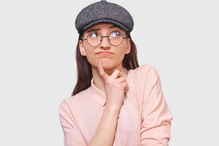 Pensive young woman wearing casual outfit and round transparent spectacles, frowning her face and  looking up to one side, poses against white studio background. People emotions concept