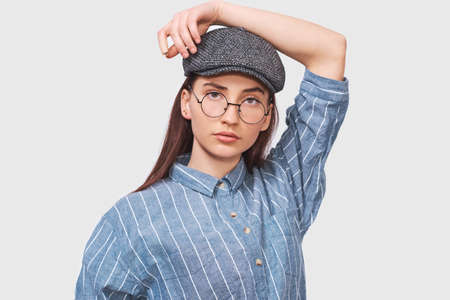 Beautiful serious female wears transparent round spectacles, casual blue shirt and gray cap, looks seriously directly into camera, poses in studio. People emotions concept