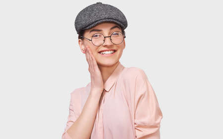 Pleased beautiful young woman, smiling broadly, wears pink shirt and round transparent eyeglasses. Pretty positive girl feels joyful posing over white studio wall. People and emotions
