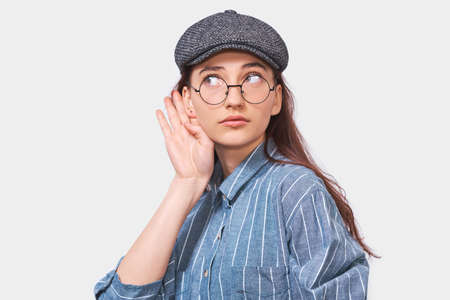 Portrait of curious teenager student paying attention and placing hand on ear asking someone to speak louder or whisper, isolated on white wall. Pretty girl which overhears secret conversation.