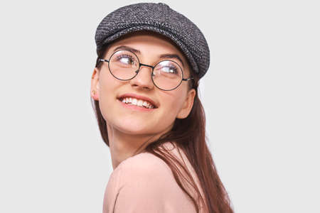 Closeup portrait of happy young woman, smiling broadly, wears pink shirt, gray cap and round transparent spectacles. Pretty girl student feels joyful and posing over white studio wall. People, emotion