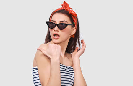 Stylish pretty young woman feeling surprised, wearing retro outfit posing over white wall. Beautiful amazed female looking through black sunglasses at someone aside. People and emotions concept