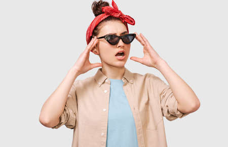 Stylish young student woman frowning her face, wearing casual outfit and blavk sunglasses. Beautiful girl looking through sunglasses with puzzled expression. People and emotions concept