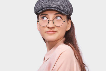 Closeup studio portrait of pleased young woman, smiling, wearing pink shirt, gray cap and round transparent eyewear. Pretty girl student feels joyful and posing over white studio wall. People, emotion Stock Photo