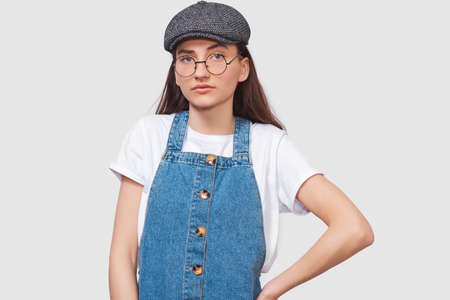 Studio image of serious young woman wears transparent trendy eyewear, casual white t-shirt, denim dress, trendy gray cap, looks seriously directly into camera, poses on white wall. People emotions