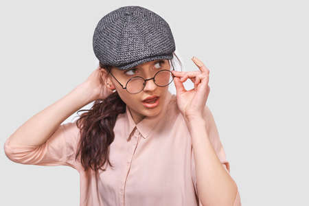 Puzzled young student woman frowning her face, wearing casual outfit and looking seriously aside. Beautiful female looking through transparent eyewear at one side. People and emotions concept Stock Photo