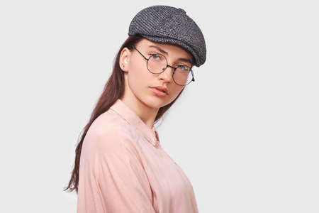 Serious young woman wears transparent spectacles, casual pink shirt and gray cap, looks seriously directly into the camera, poses against white studio background. People emotions concept Stock Photo