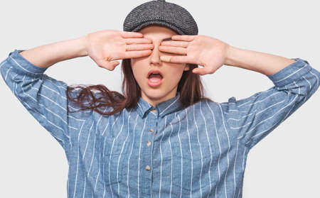 European young woman in casual outfit, covering her eyes, has a surprised face, waiting for a surprise for her birthday. Playful female playing hide, seek and peek a boo with her child. Stock Photo