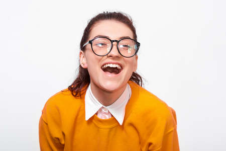 Closeup studio portrait of happy young woman, smiling broadly, wears orange sweater and round transparent spectacles. Pretty girl student posing over white studio wall. People and emotions