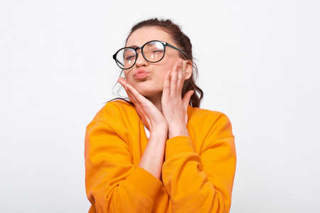 Charming teenager girl blowng air kiss, wears orange sweater and round transparent eyeglasses. Positive student feels joyful posing over white studio wall. People and emotions Stock Photo